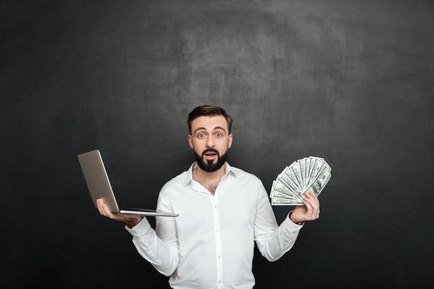 Retrato de homem adulto surpreso na camisa branca, segurando o leque de notas de dólar de dinheiro e caderno de prata em ambas as mãos sobre cinza escuro Foto gratuita