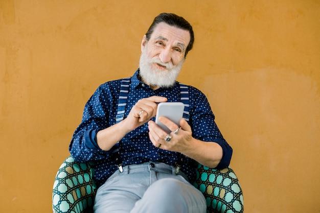 Retrato de homem barbudo sorridente sênior agradável, vestindo calças e camisa elegantes, sentado no fundo amarelo e usando o telefone Foto Premium