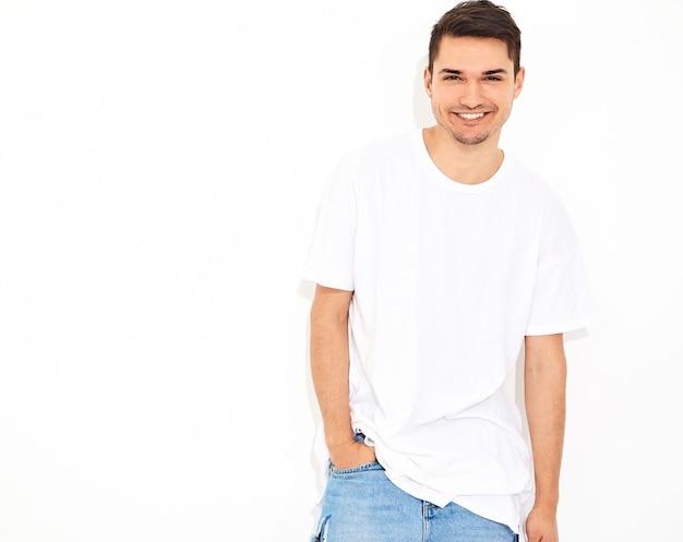 Retrato de homem bonito modelo jovem sorridente, vestido com roupas jeans e posando de t-shirt. tocando sua cabeça Foto gratuita