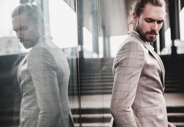 Retrato de homem bonito sexy vestido elegante terno xadrez bege Foto gratuita