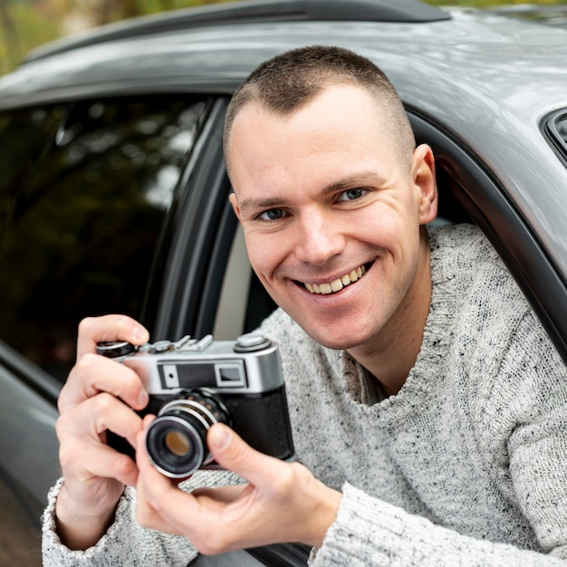 Retrato de homem bonito, usando uma câmera vintage Foto gratuita
