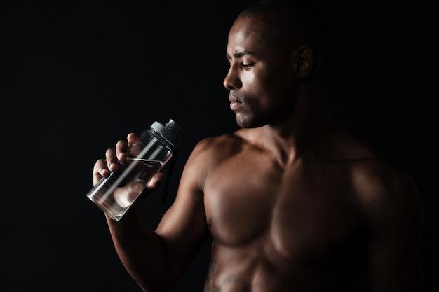 Retrato de homem cansado de esportes afro-americanos jovens, segurando a garrafa de água Foto gratuita