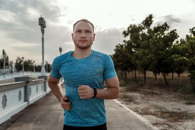 Retrato de homem caucasiano em uma camiseta azul e calção preto que treina e corre na pista de asfalto durante o pôr do sol Foto Premium