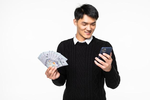 Retrato de homem chinês animado com telefone nas mãos, mostrando muitas notas isoladas na parede branca Foto gratuita