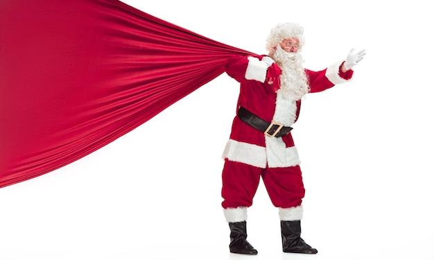 Retrato de homem com fantasia de papai noel - com uma luxuosa barba branca, chapéu de papai noel e uma fantasia vermelha - de corpo inteiro isolado em um fundo branco com um grande saco de presentes Foto gratuita