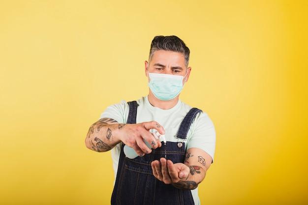 Retrato de homem com máscara protetora e tatuagens usando gel desinfetante para lavar as mãos contra a prevenção de coronavírus Foto Premium
