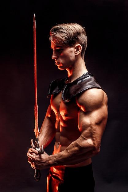 Retrato de homem concentrado muscular sexy segurando a espada. Foto Premium