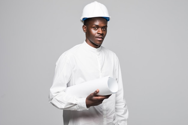 Retrato de homem confiante, sorridente, afro-americano arquiteto com planta, olhando para a câmera isolada em fundo cinza Foto gratuita