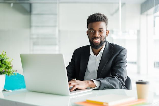 Retrato de homem de negócios jovem negro africano bonito trabalhando no laptop na mesa de escritório Foto gratuita