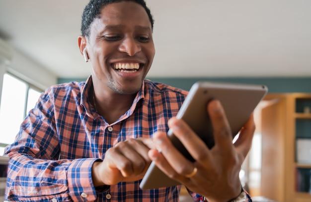 Retrato de homem de negócios, trabalhando em casa com tablet digital. conceito de escritório em casa. novo estilo de vida normal. Foto gratuita