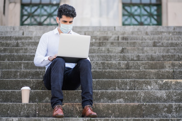 Retrato de homem de negócios usando máscara facial e usando seu laptop enquanto está sentado na escada ao ar livre Foto gratuita