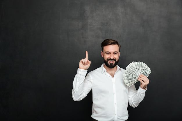 Retrato de homem de sorte na camisa branca, segurando muito dinheiro em dinheiro na mão e aparecendo o dedo sobre cinza escuro Foto gratuita