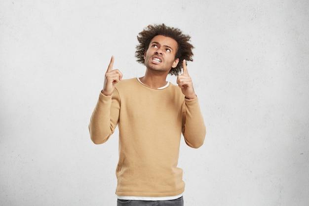 Retrato de homem descontente com penteado espesso, aperta os dentes e indica de cabeça para cima Foto gratuita