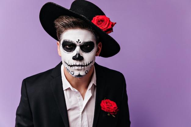 Retrato de homem em assustadora máscara de estilo mexicano, olhando severamente para a câmera. Foto gratuita