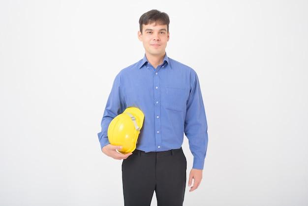 Retrato de homem engenheiro com capacete de segurança amarelo está no branco Foto Premium