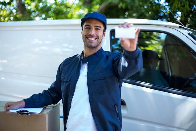 Retrato de homem entrega sorridente, mostrando o cartão de visita Foto Premium