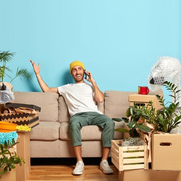 Retrato de homem feliz conversa ao telefone, gesticula com uma das mãos, tenta explicar o caminho para seu novo apartamento e usa chapéu amarelo Foto gratuita