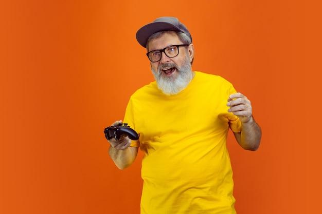 Retrato de homem hippie sênior usando dispositivos, gadgets isolados em fundo laranja do estúdio. tecnologia e conceito de estilo de vida idoso alegre. t Foto gratuita