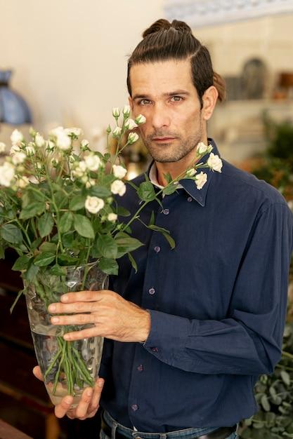 Retrato de homem jardineiro com cabelos compridos, segurando flores Foto gratuita