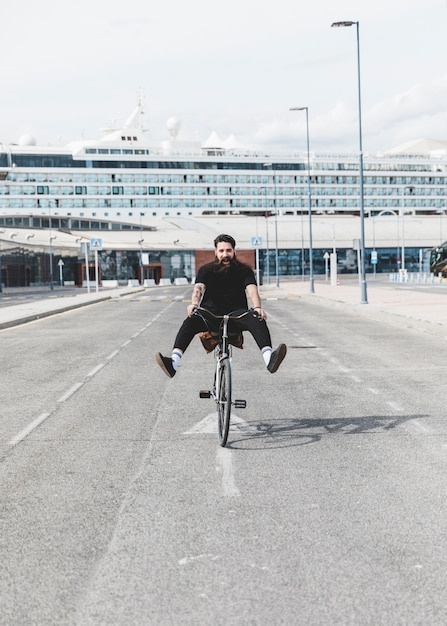 Retrato, de, homem jovem, bicicleta equitação, ligado, estrada, com, pernas, expulso, frente, cruzeiro Foto gratuita