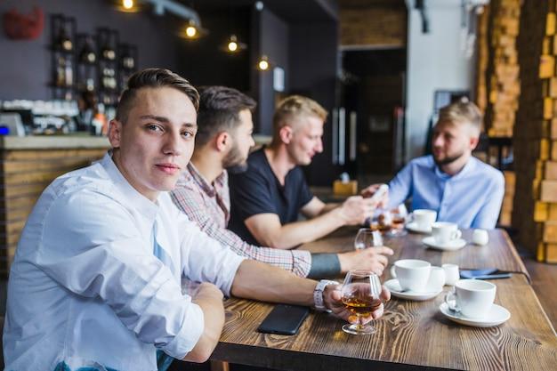 Retrato, de, homem jovem, com, seu, amigos, copo segurando, de, bebida Foto gratuita