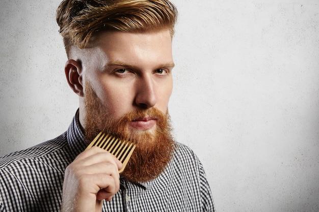 Retrato de homem jovem e atraente ruiva hipster com olhar sério e confiante, segurando o pente de madeira e fazendo sua barba espessa. barbeiro barbudo elegante em camisa quadriculada penteando no salão. Foto gratuita
