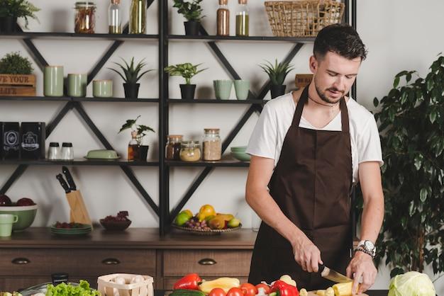 Retrato, de, homem jovem, legumes cortantes, com, faca, cozinha Foto gratuita