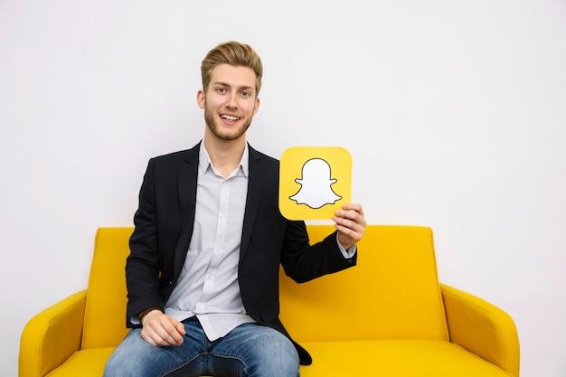 Retrato, de, homem jovem, sentar sofá amarelo, segurando, snapchat, ícone Foto gratuita