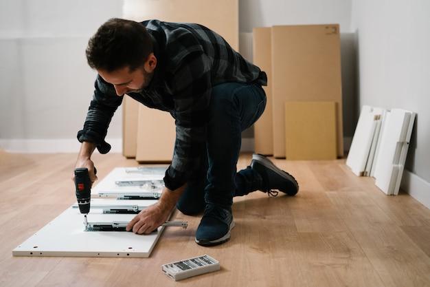 Retrato de homem montando móveis. faça você mesmo a montagem dos móveis. Foto Premium