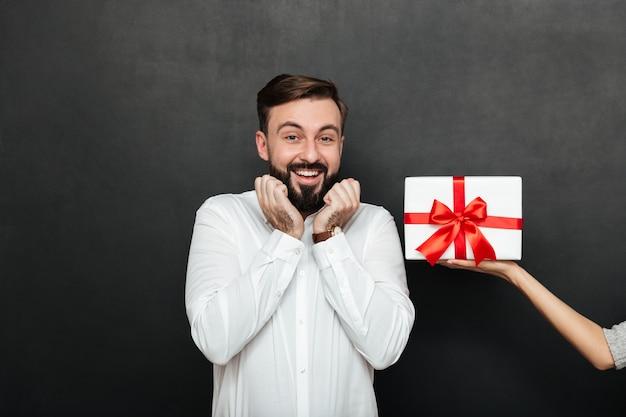 Retrato de homem morena animado, regozijando-se em obter caixa de presente branca com laço vermelho da mão feminina sobre parede cinza escura Foto gratuita