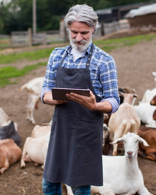 Retrato de homem na fazenda olhando no tablet Foto gratuita
