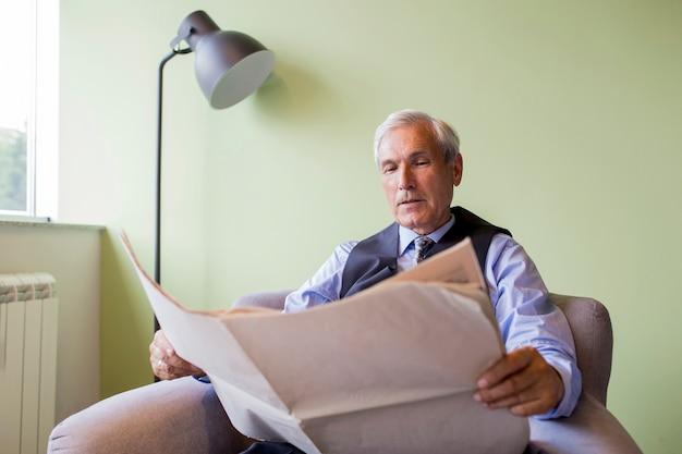 Retrato, de, homem negócios sênior, sentando, ligado, poltrona, jornal leitura Foto gratuita