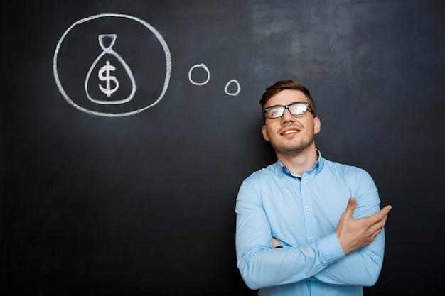 Retrato de homem ocupado cruzou as mãos sobre o dinheiro de lousa conc Foto gratuita