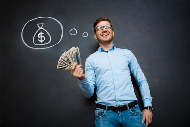 Retrato de homem ocupado segurando dólares nas mãos sobre o quadro-negro Foto gratuita