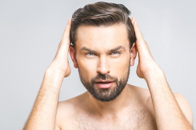 Retrato de homem saudável feliz, penteando o cabelo com os dedos Foto Premium