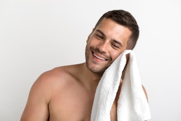 Retrato de homem sem camisa sorridente, limpando o rosto com uma toalha branca Foto gratuita
