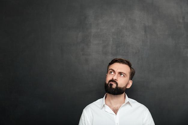 Retrato de homem sério morena de camisa branca, olhando para cima com o rosto retorcido, pensando ou recordando sobre cinza escuro Foto gratuita