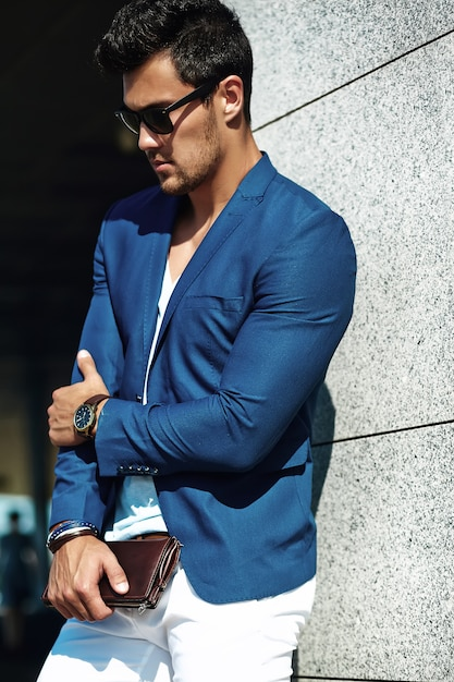 Retrato de homem sexy modelo masculino bonito vestido elegante terno posando no fundo da rua Foto gratuita