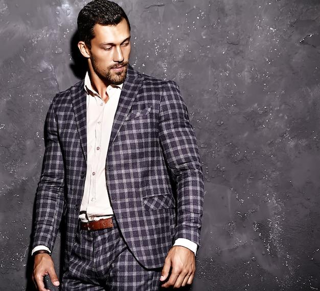 Retrato de homem sexy modelo masculino bonito vestido elegante terno posando perto da parede cinza Foto gratuita