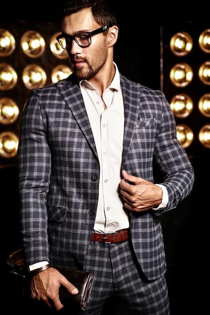 Retrato de homem sexy modelo masculino moda sexy vestido elegante terno em fundo preto luzes de estúdio em copos Foto gratuita
