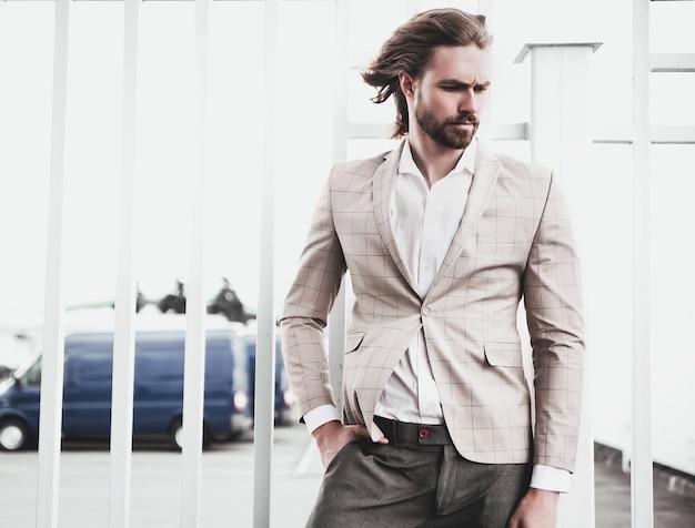 Retrato de homem sexy modelo masculino moda sexy vestido elegante terno xadrez bege posando no fundo da rua Foto gratuita