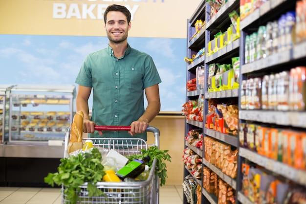 Retrato, de, homem sorridente, andar, com, seu, bonde, ligado, corredor Foto Premium