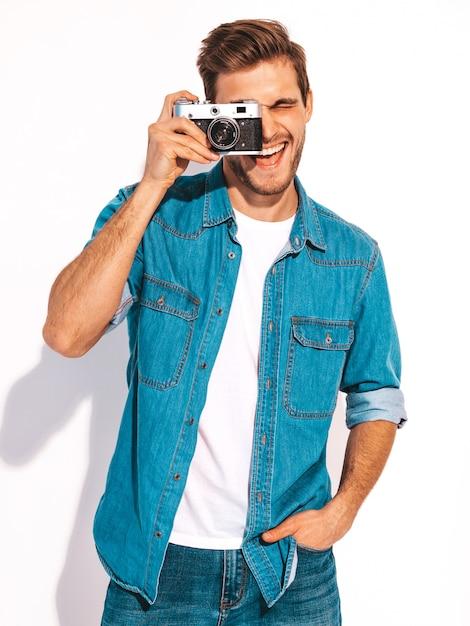 Retrato de homem sorridente bonito vestindo roupas jeans de verão. modelo masculino tirando foto na câmera fotográfica vintage velha. Foto gratuita