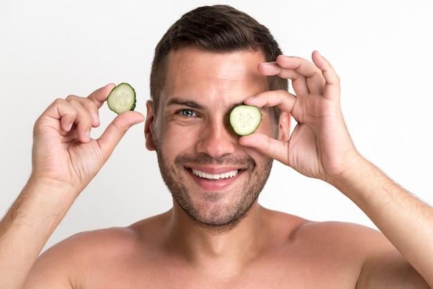 Retrato, de, homem sorridente, segurando, e, escondendo, olho, com, pepino, fatia Foto gratuita