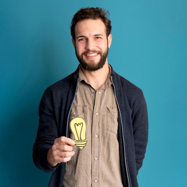 Retrato de homem sorridente segurando luz idéia Foto gratuita