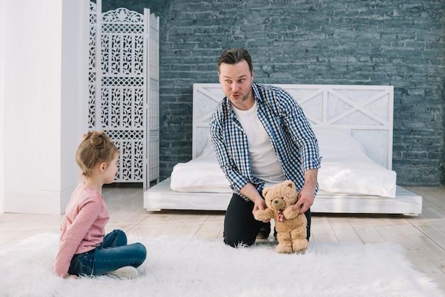 Retrato, de, homem, tocando, com, filha, em, quarto Foto gratuita
