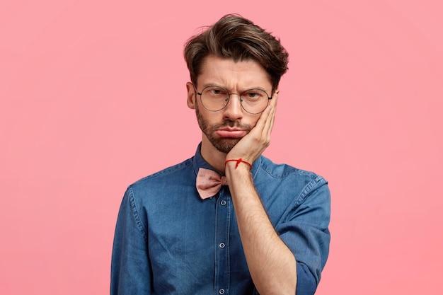 Retrato de homem triste e estressante mantém a mão na bochecha, parece desesperado, sente dor de dente, tem alguns problemas Foto gratuita