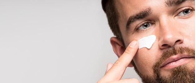 Retrato de homem usando creme facial com espaço de cópia Foto gratuita