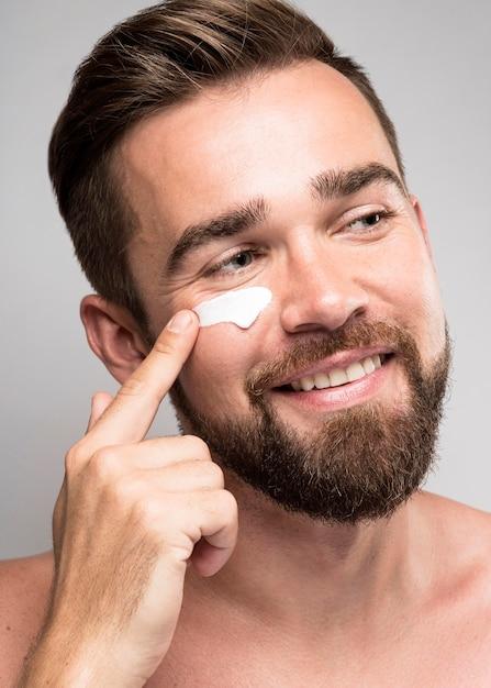Retrato de homem usando creme facial Foto gratuita