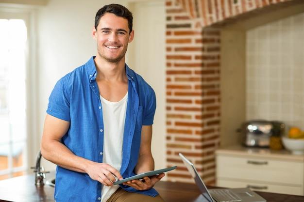 Retrato, de, homem, usando, tablete digital, com, laptop, em, cozinha Foto Premium